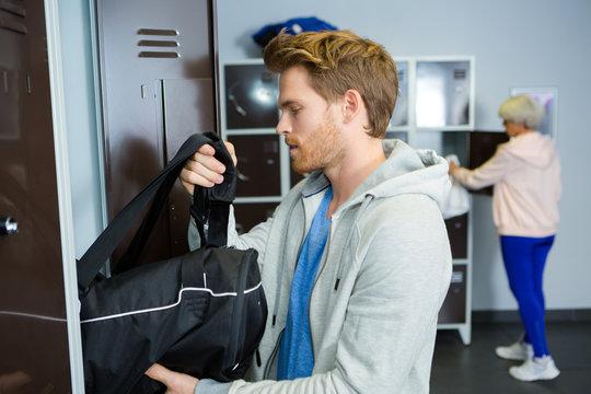 sportsman taking bag from locker