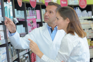 male pharmacist helping female customer in store