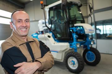 Portrait of mechanic, vineyard vehicle in background