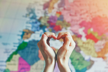 Spoed Fotobehang Wereldkaart hand in heart shape with love on world map background