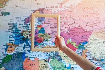 hand holding empty wooden frame on Europe map background