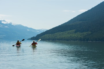 Rear view of couple kayaking in lake against sky