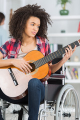handicapped woman playing the guitar