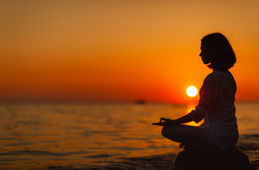 Wall Mural - woman practices yoga and meditates in lotus position on sunset beach.