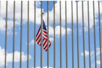 The USA flag visible through fence grates