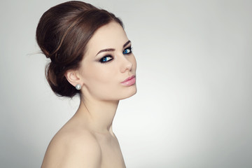 Young beautiful woman with stylish make-up and hair bun