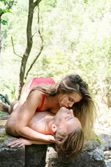 Sexy naked couple lying on stone in nature and kissed with a lot of passion
