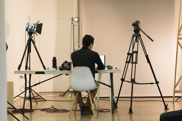Rear view of photographer working in studio