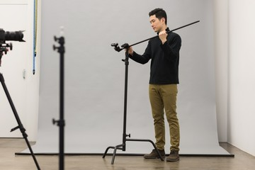 Full length of photographer adjusting tripod