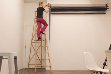 Full length of man on ladder adjusting backdrop