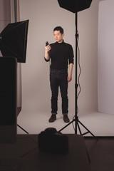 Full length of photographer holding camera flash