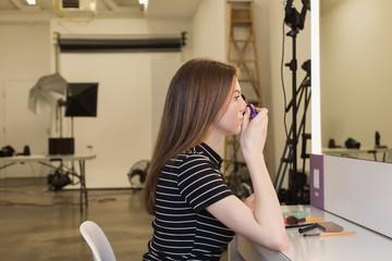 Side view of beautiful woman applying mascara