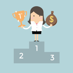 Businesswoman standing on the winning podium holding trophy and a bag of money