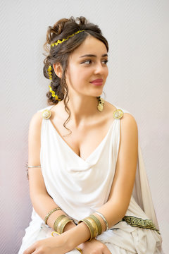 portrait of charming young greek woman in antique white dress looking side