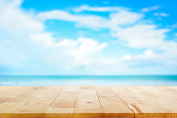 Wood table top on blur blue sea and sky background