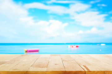 Wood table top on blur summer sky and sea with banana boats as background