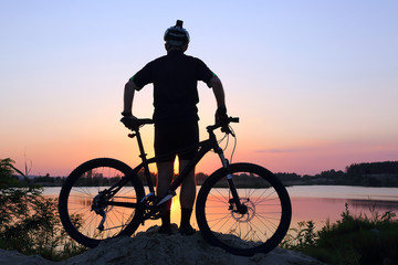 silhouette of the cyclist looking at the sunset on the pond.