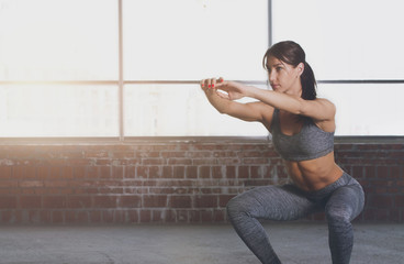 Young woman athlete in sportswear squat on gymnastic ball