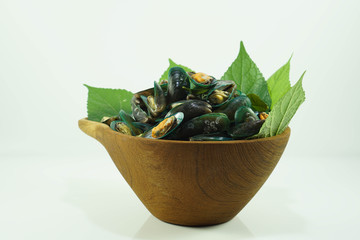 Stream mussels seafood with leaf in wooden bowl isolated white background