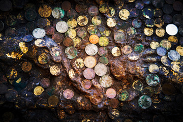 Many coin stick on old stone plate in old temple of Thailand