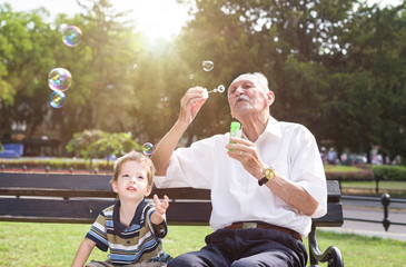 grandfather blowing soap bubbles to his grandchild