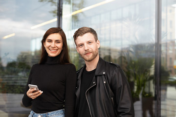 Happy cute young couple walking outdoors. Attractive unshaven hipster in black leather jacket having date with beautiful brunette woman who is standing next to him and using electronic device
