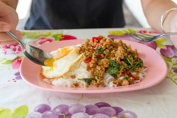 Women eating Basil pork rice and fried egg