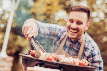 Young man cooking meat on barbecue