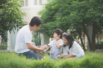 Happy Asian family playing with siberian husky dog