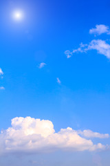 Blue sky background with white clouds and sunlight with lens flare on sunny summer or spring day.