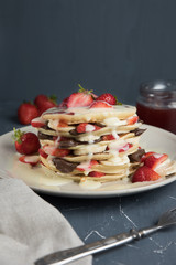 Delicious pancakes on grey table with fruits. Plate full of pancakes with strawberries, bananas and chocolate cream. Pouring over by Syrup. Berry jam in glass jar