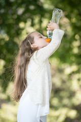 Lovely little girl drinking water