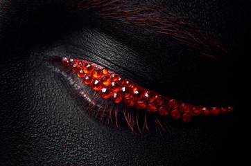 Macro and close-up creative make-up theme: beautiful female eye with black skin and red diamonds, retouched photo