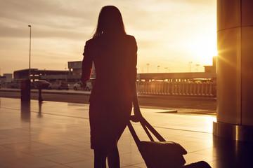 Frau mit Trolley bei Sonnenuntergang