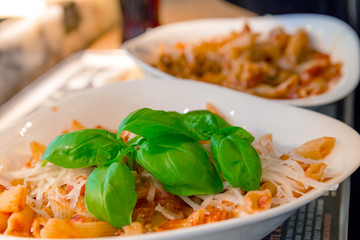 Penne pasta with tomato sauce and decorated with a mint leaf