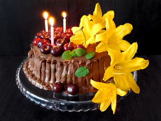 Chocolate cake decorated with cherries, candles and flowers for a birthday party