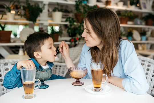 Mom feeds his little son to ice cream in  light cafe