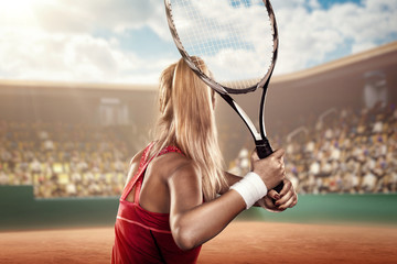 back view of a female tennis player on tennis court ready to hit a ball