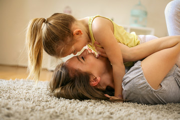 Single mother playing with her little daughter.