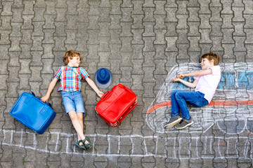 Two little kids boys having fun with train picture drawing with colorful chalks on ground