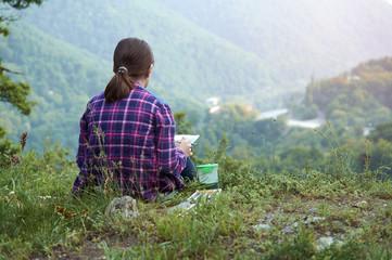 Young girl drawing a beautiful mountain landscape
