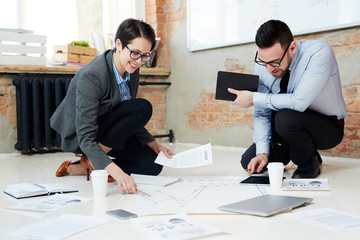 Two analysts working with papers on the floor