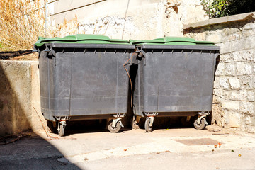 Old metal garbage containers on the street, trash dumpsters. Dirty refuse bins. Street scene.