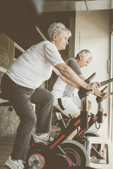 Two senior people working out on elliptical machine.