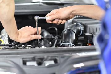 Closeup: Reparatur Auto durch Mechaniker in einer Werkstatt // Repair car by mechanic in a workshop