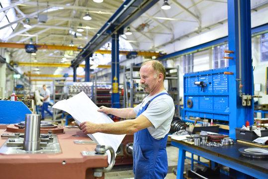 Monteur im Maschinenbau studiert technische Zeichnung für die Montage von Getrieben // Mechanical engineer studying technical drawing for the assembly of gearboxes