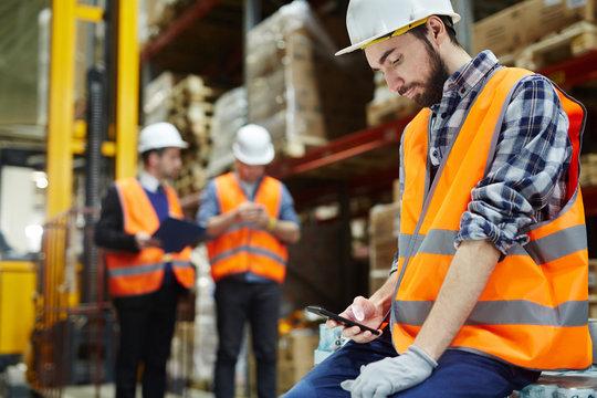 Man in uniform and helmet messaging at break in warehouse