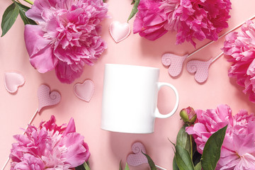 White coffee mug with peonies and hearts on pink background.