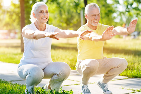 Positive aged couple doing squats in the park