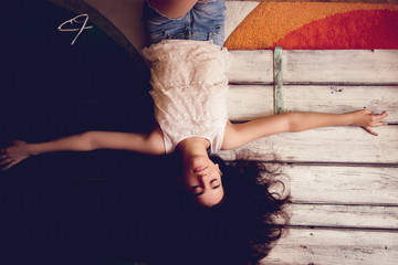 Teenage girl lying and daydreaming with arms outstretched